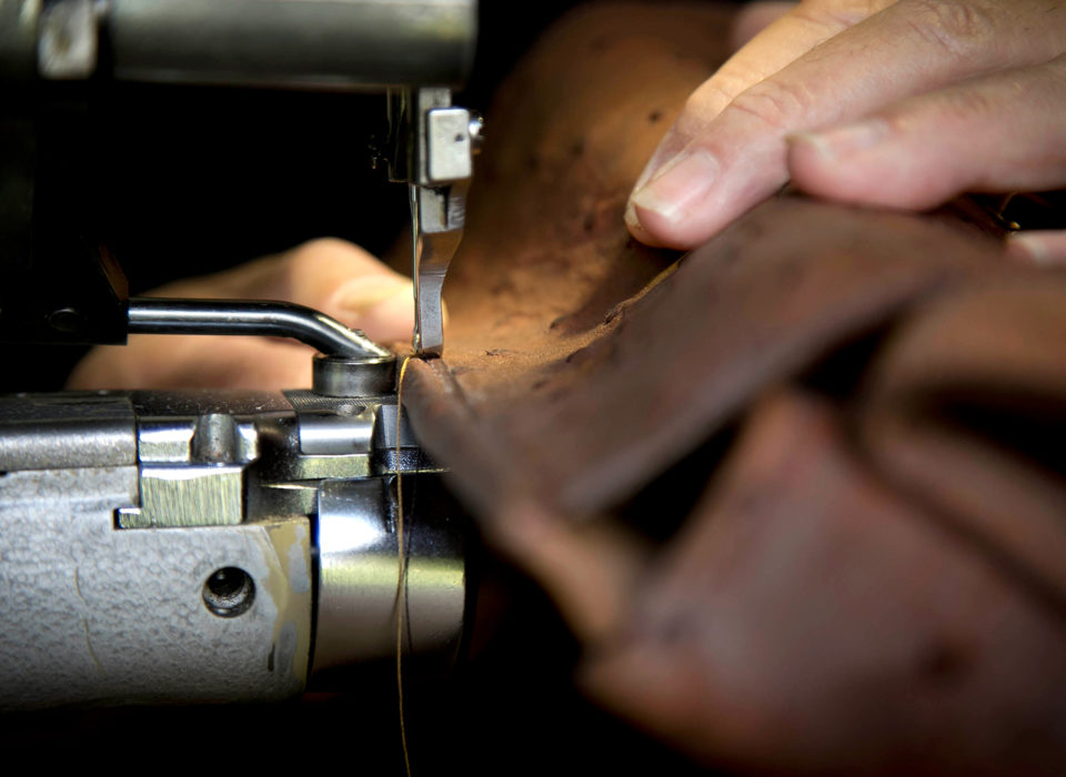 artisan maroquinier cousant un sac dans son atelier