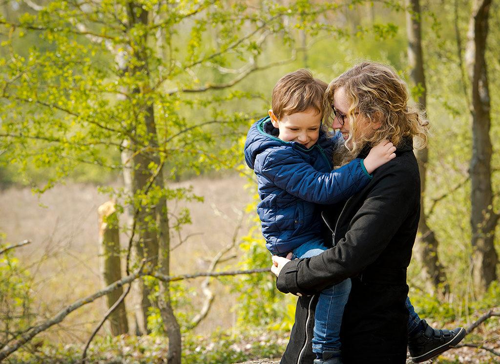 un petit garçon est dans les bras de sa maman