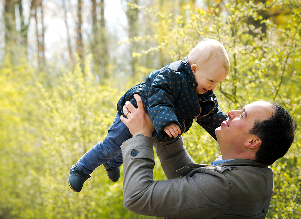 un père est en train de lancer sa fille en l'air