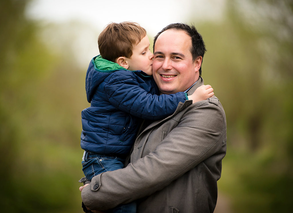 un petit garçon dans les bras de son père et lui faisant un bisou
