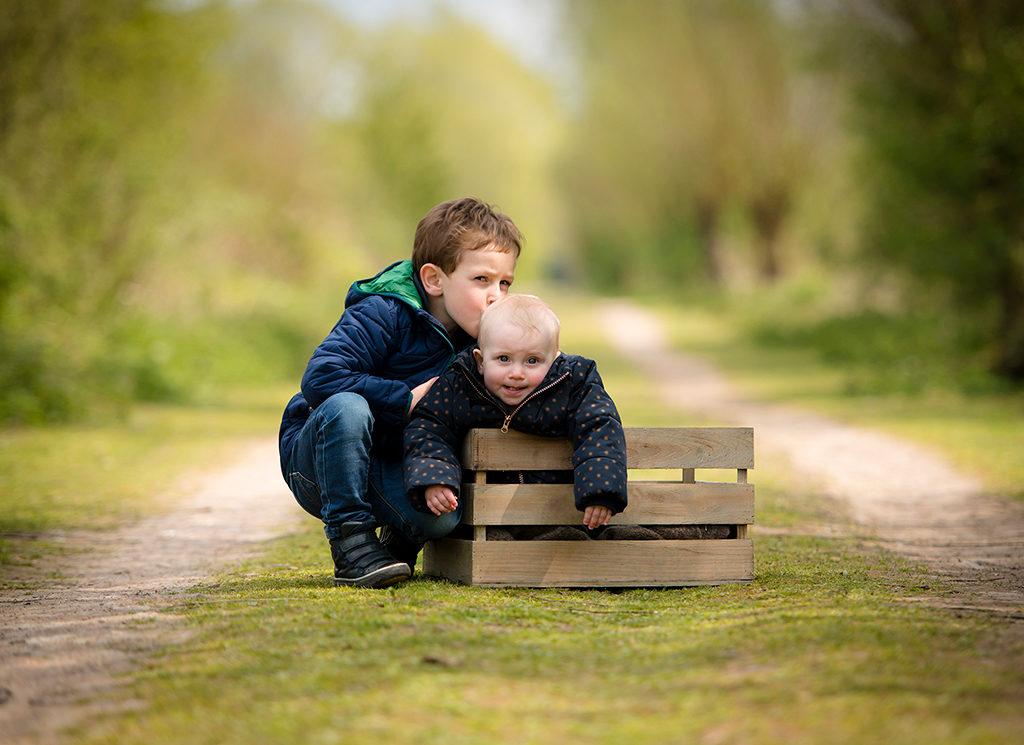 une petite fille de 1 an assise dans une caisse en bois et à côté d'elle son frère est accroupi et lui fait un bisou sur la tête