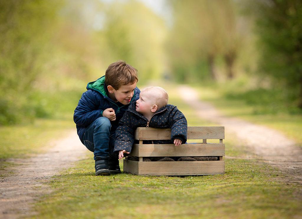 une petite fille de 1 an assise dans une caisse en bois et à côté d'elle son frère est accroupi