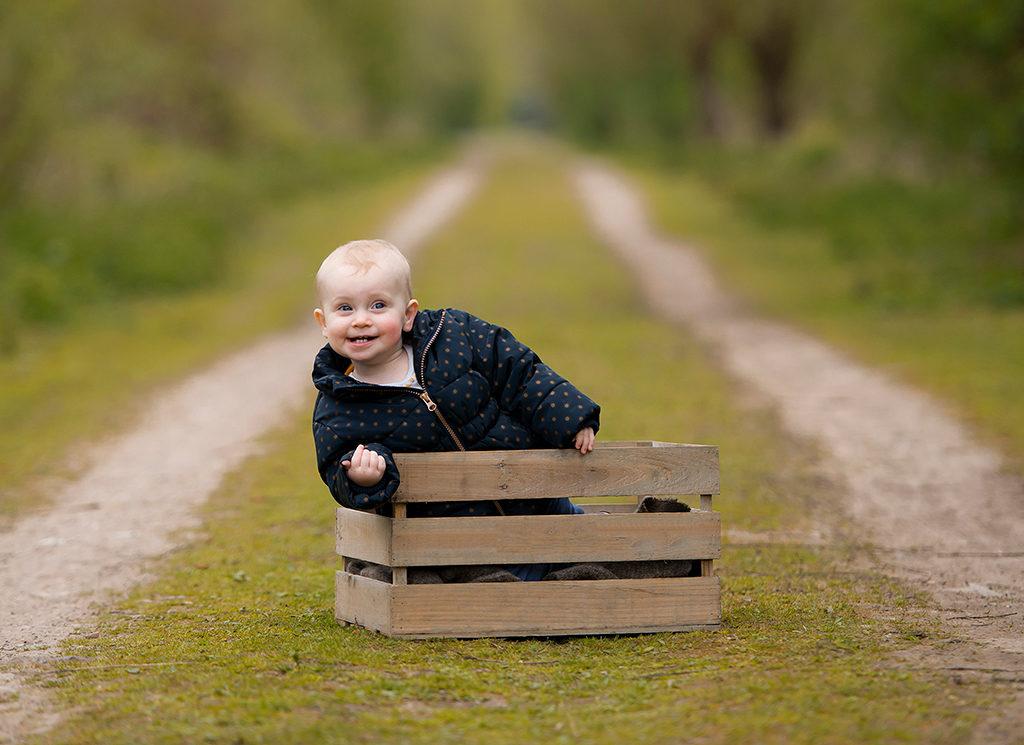 une petite fille de 1 an assise dans une caisse en bois dans les marais de Fretin