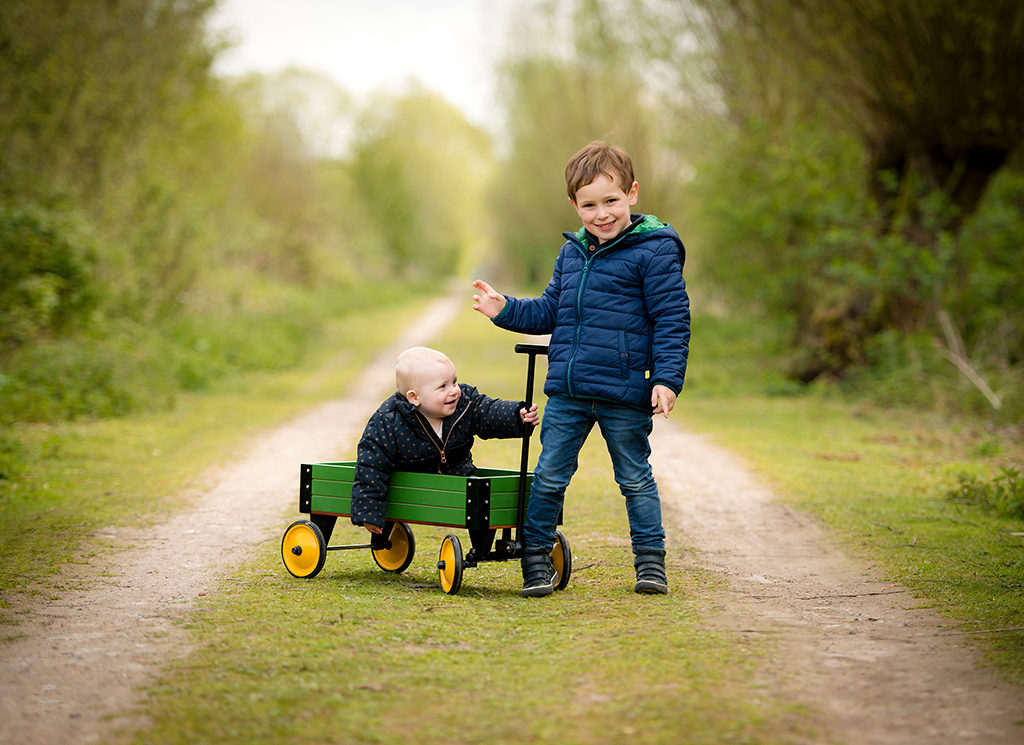 un petit garçon tire sa soeur assise dans un chariot vert et jaune