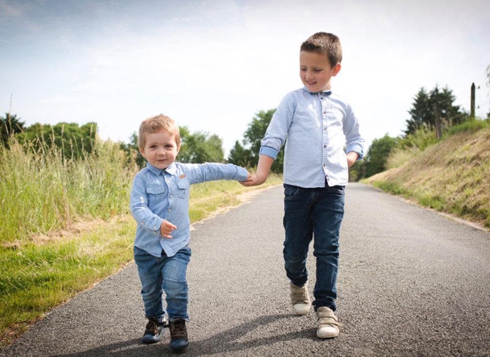 des enfants qui se baladent main dans la main dans la campagne