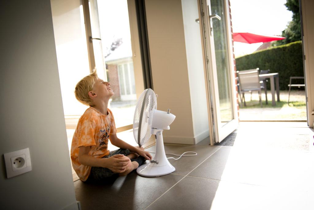 des enfants qui s'amusent avec un ventilateur à leur maison