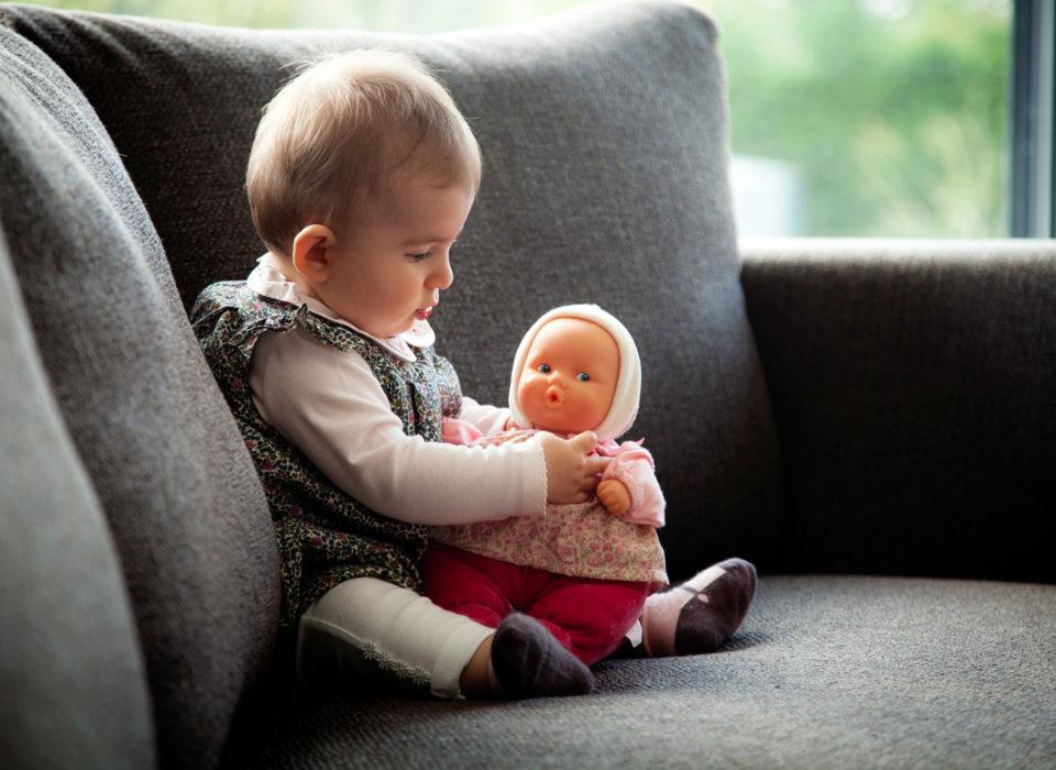 un bébé qui joue avec sa poupée assis dans un fauteuil