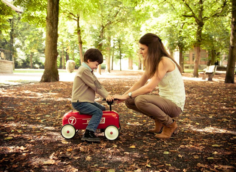 un fils en balade sur une voiture avec sa mère dans un parc
