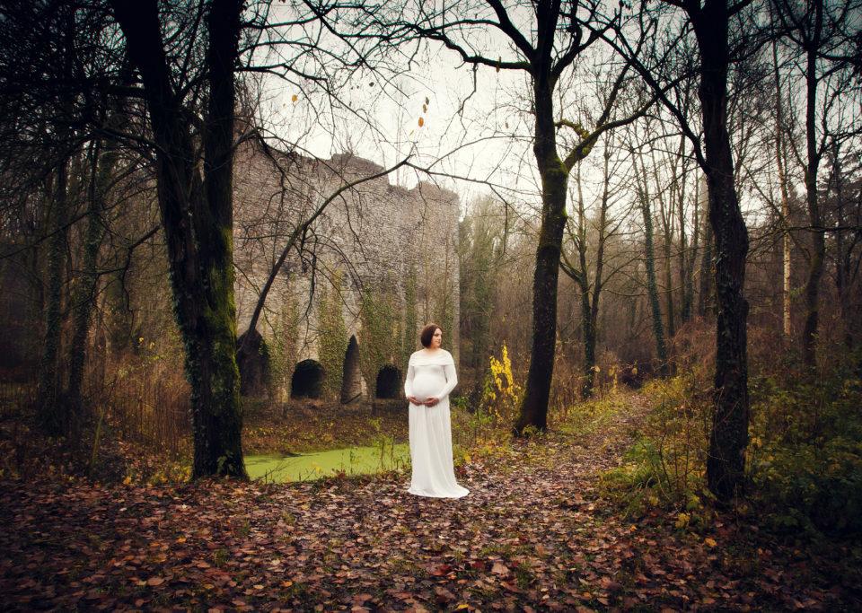 femme enceinte en forêt avec ruine en arrière plan