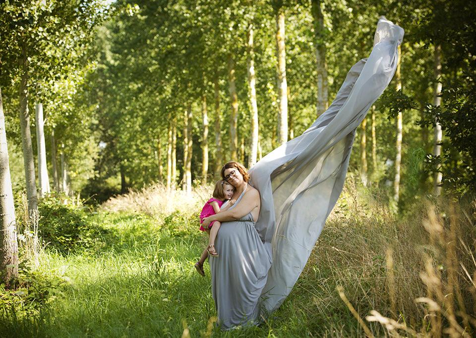 femme enceinte portant une robe grise dans les bois