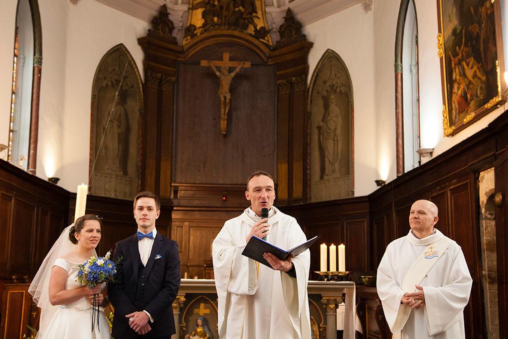 homélie du prêtre habillé en blanc qui tient un livre dans ses mains lors d'un mariage