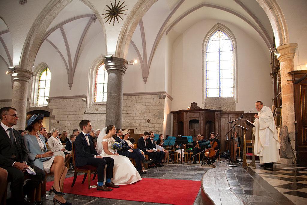 Prêtre réalisant la cérémonie religieuse du marié avec des chaussettes bleues et de la mariée avec son bouquet de fleurs bleues