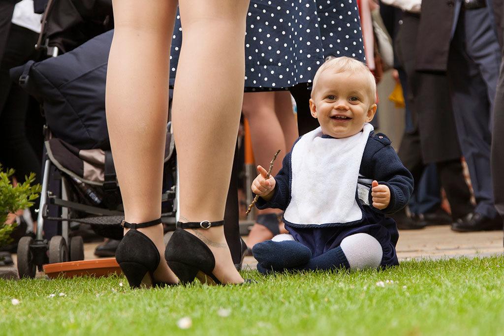 un bébé assis par terre pendant le vin d'honneur d'un mariage