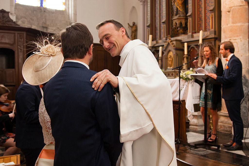 le prêtre sert la main du papa du marié à la fin de la cérémonie religieuse