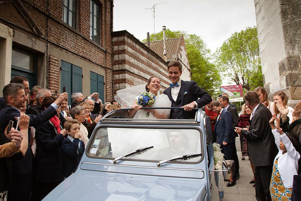 des mariés dans leur voiture coccinelle bleue à la sortie de la cérémonie religieuse