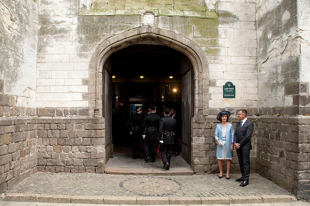 la maman et le papa habillés en bleu et gris du marié attendent leur fils à l'entrée de l'église