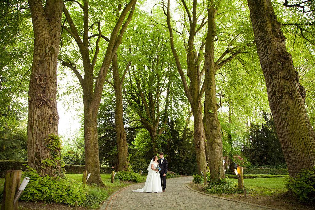 les mariés dans l'allée du Clos de la conciergerie pour leur séance de couple
