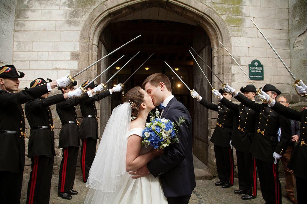 des mariés habillés avec une touche de bleu s'embrassent à la sortie de l'église