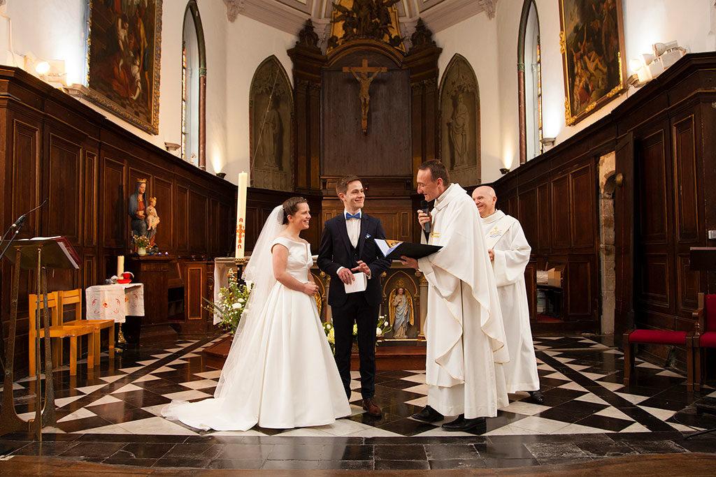 le prêtre avec un livre dans les mains accueille les mariés pour la cérémonie religieuse