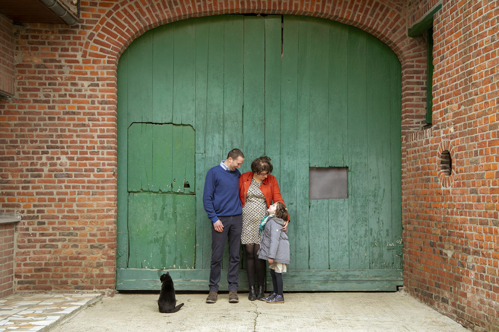 un couple et leur fille qui posent devant une porte en bois verte dans une ferme