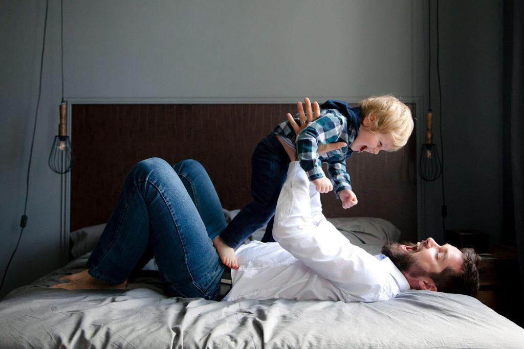 Un père et son fils en train de jouer sur un lit