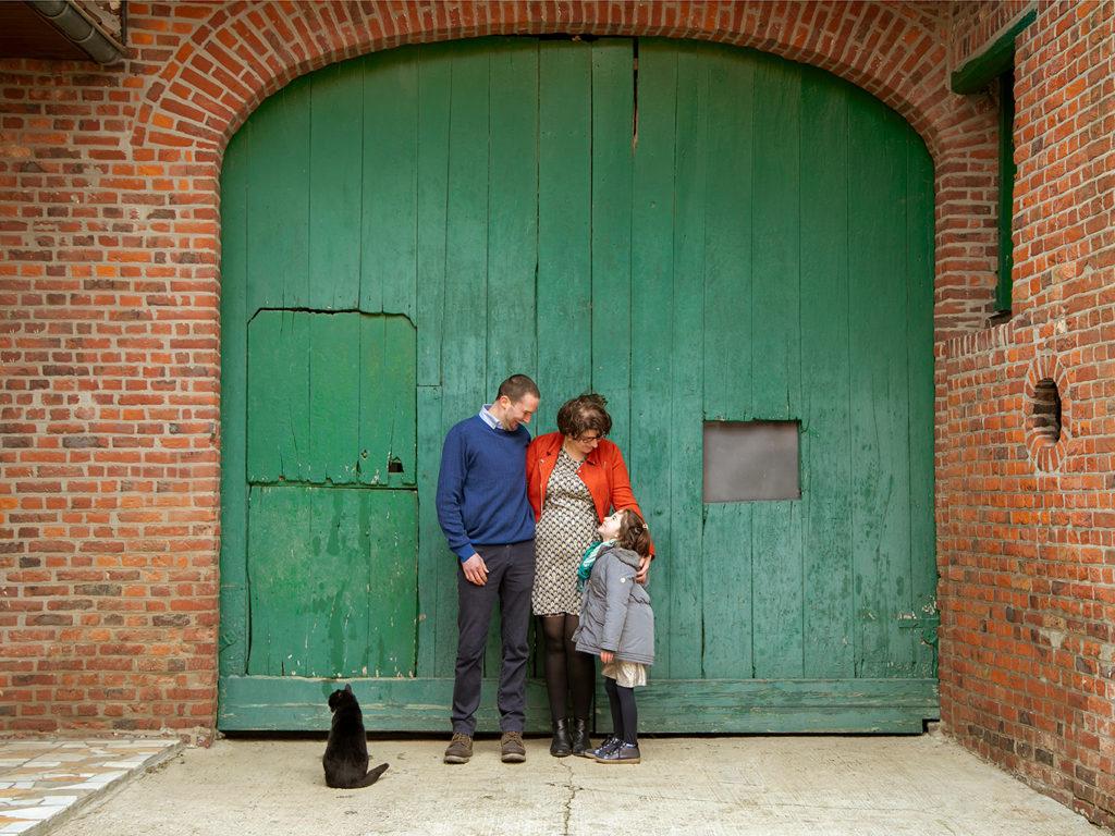 photo de famille avec leur chat dans une ferme devant une porte en bois verte
