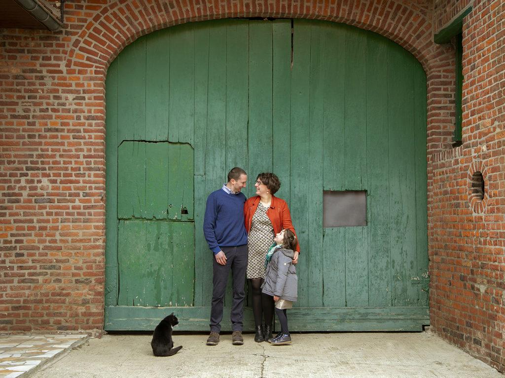 un père , une mère et leur fille qui posent devant une porte en bois verte