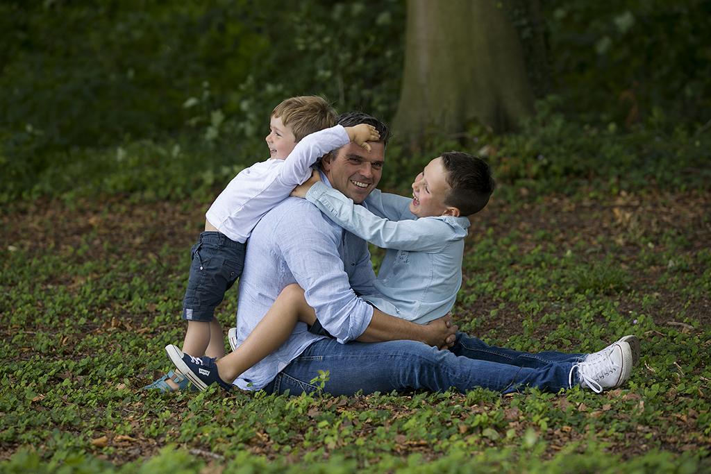 un père assis dans l'herbe avec ses 2 fils sur ses genoux