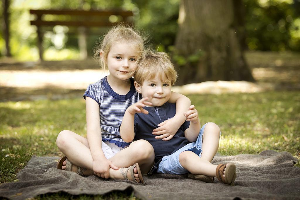 un frère et une soeur assis dans l'herbe