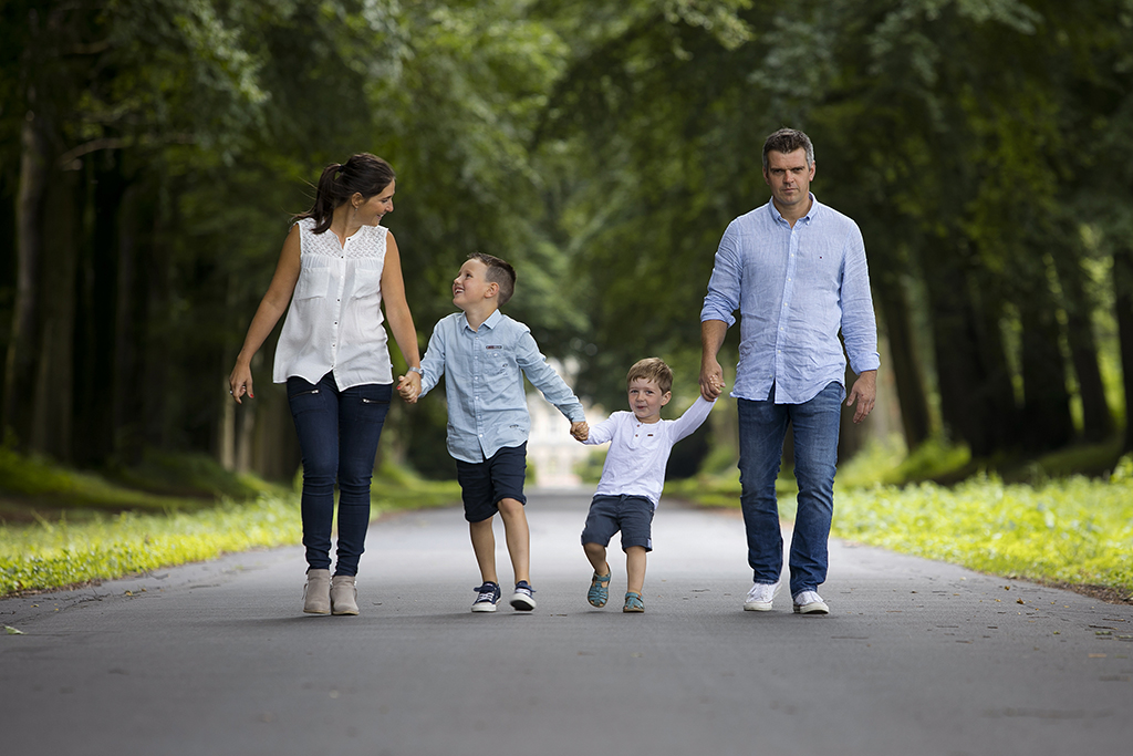 photographies de famille avec deux enfants marchant main dans la main dans une allée arborée