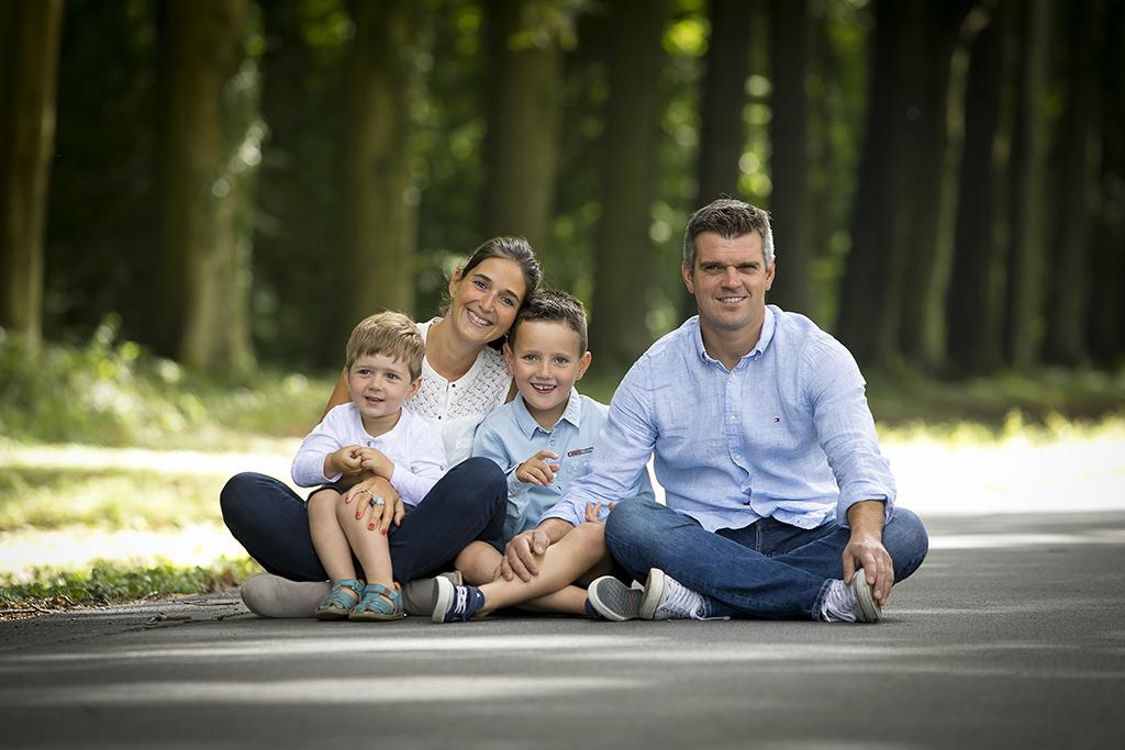 photographies de  famille avec deux enfants assis dans une allée arborée