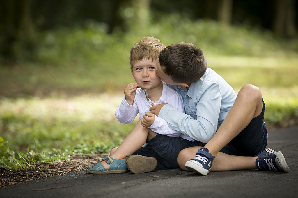 un grand frère en train d'embrasser son petit frère