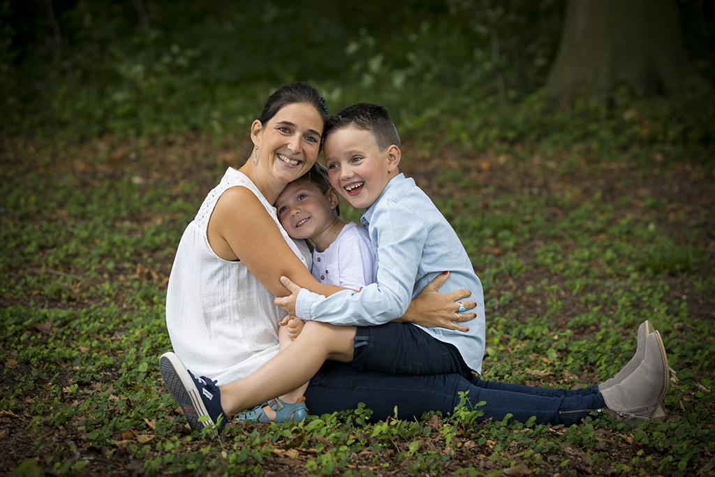 une mère assise dans l'herbe avec ses 2 fils sur ses genoux