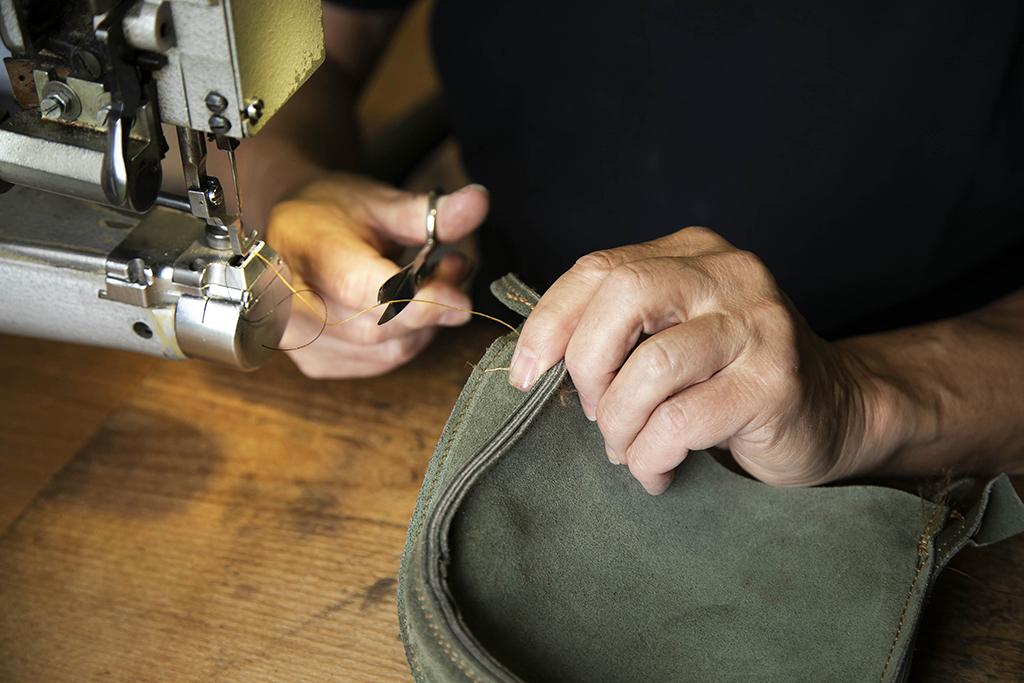un artisan  cousant un sac à main