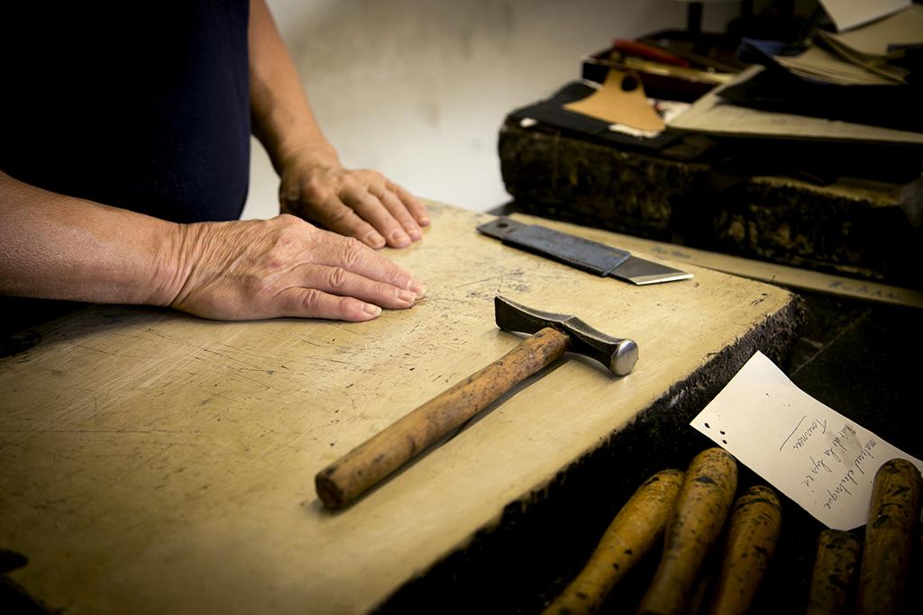 un artisan  en train de fabriquer un porte monnaie