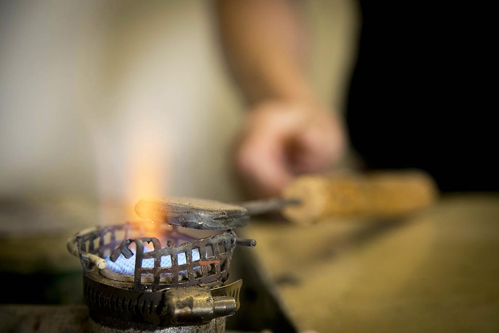 un artisan maroquinier en train de fabriquer un porte monnaie