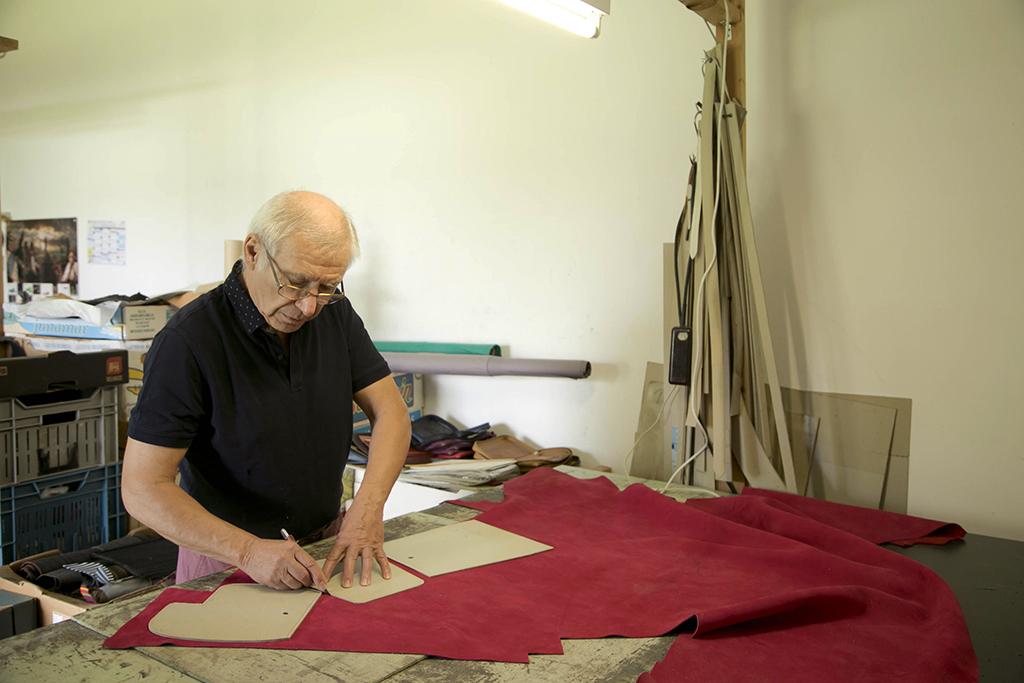un artisan maroquinier en train de couper de la suédine