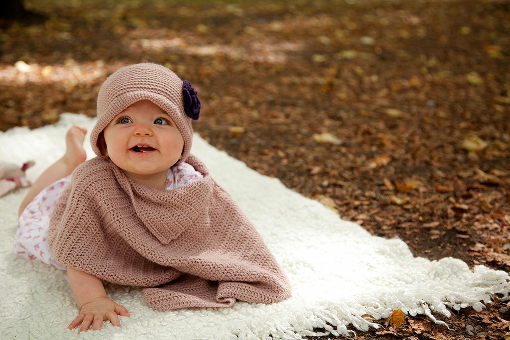 petite fille sur une couverture dans un parc