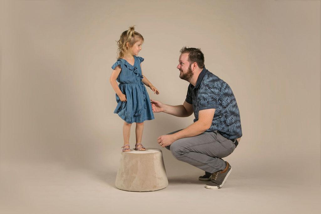 photo en studio d'une petite fille debout sur un tabouret qui joue avec son papa